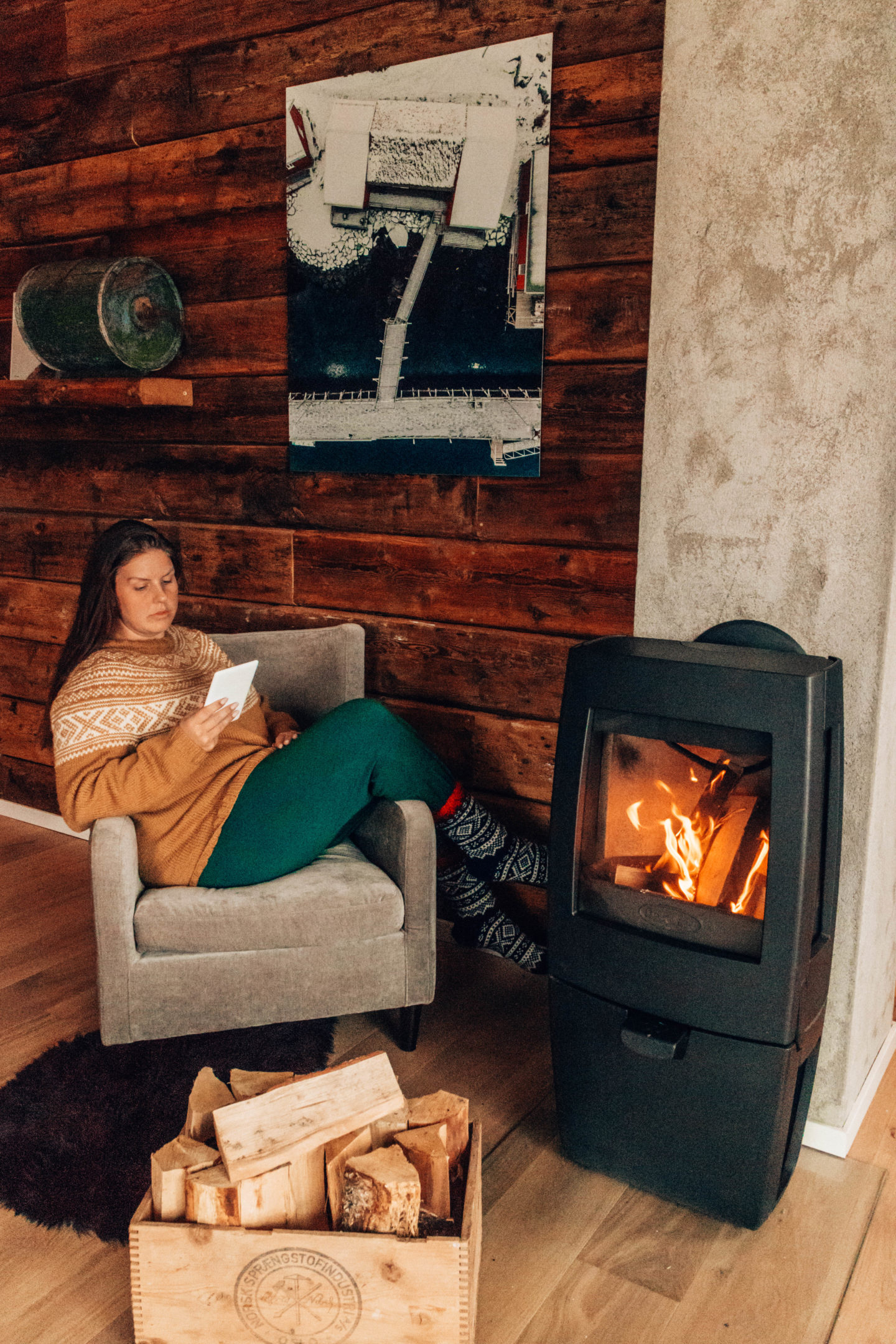 girl in nordic sweater reading by the fireplace in norway